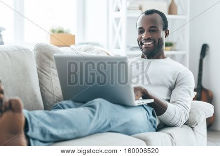 Relaxation at home. Handsome young African man looking at laptop and smiling while lying on the sofa at home