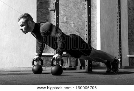 Developing strength. Good looking professional well built sportsman working out in the gym and developing his strength while using special sports equipment