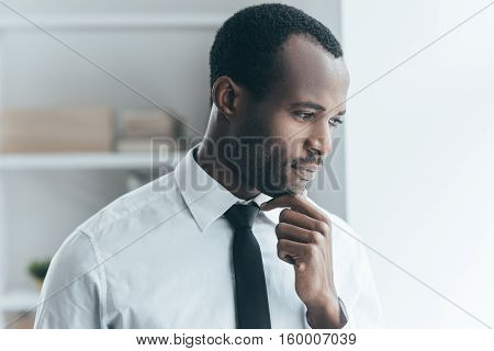 Thinking about new solutions. Handsome young African man holding hand on chin and looking away while standing in creative office