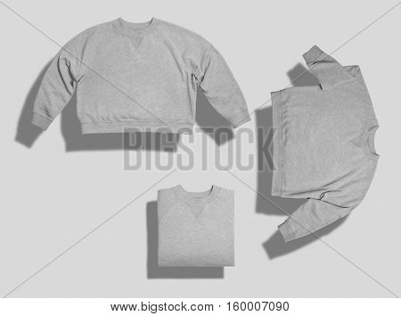 Set of three shots of light heather gray blank short sweatshirt arranged in different ways on white background