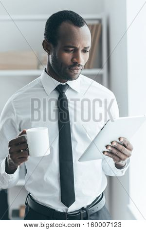 Drinking coffee during working day. Handsome young African man in formalwear holding a cup and looking on digital tablet while standing in creative office