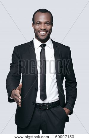 Good to see you in our team! Handsome young African man in formalwear man stretching out hand for shaking and smiling while standing against grey background