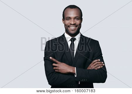 Pointing somewhere. Handsome young African man in formalwear pointing somewhere and smiling while standing against grey background