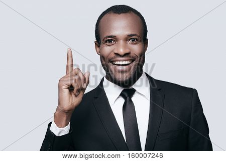 I have an idea! Handsome young African man in formalwear pointing up and smiling while standing against grey background