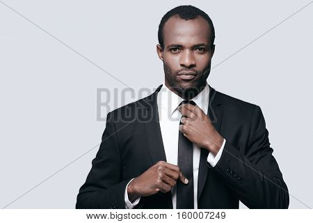 Perfect businessman. Portrait of confident young African man adjusting his necktie while standing against grey background