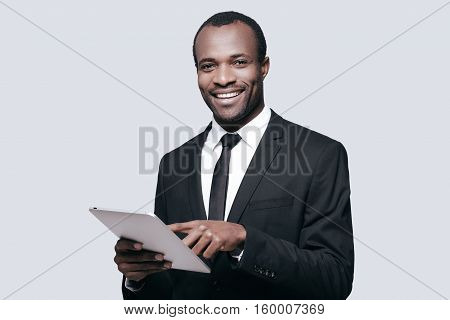 Feeling happy about work. Handsome young African man smiling and using digital tablet while standing against grey background