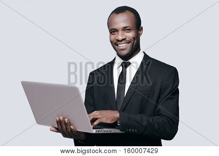 Success achieved! Handsome young African man in formalwear working on laptop while standing against grey background
