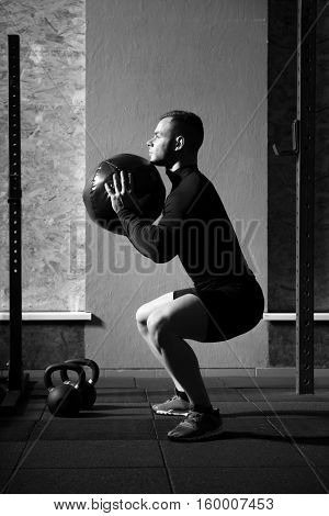 Special sports equipment. Muscular hard working handsome man squatting and holding a med ball while doing a physical exercise in the gym