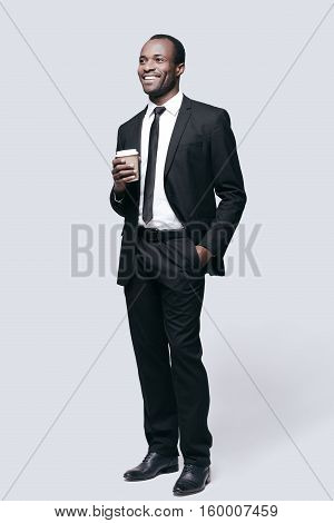 On coffee break. Full length of handsome young African man looking away and smiling while standing against grey background