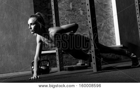 Be always fit. Serious sporty well built woman holding one hand behind her back and doing push ups while keeping herself physically fit