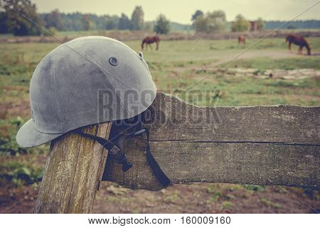 Jockey helmet hanging on the fence of the old ranch