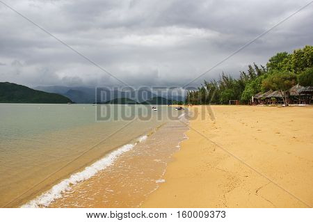 beautiful views of the sea and beach of Vietnam, transparent clear water, wide Golden beach, lots of greenery and umbrellas with thatched roof, on the horizon, the hills, the overcast sky with clouds