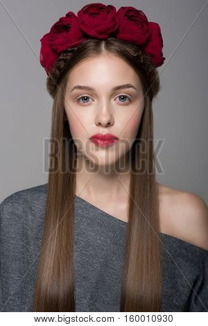 Portrait of a beautiful young girl with natural make-up, long silky hair and a wreath of red roses on her head. Isolated on gray background