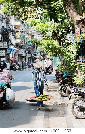Vietnam, Hue - October 21, 2016: Vietnamese woman carrying baskets of fruit and vegetables on the street in Hue, Vietnam