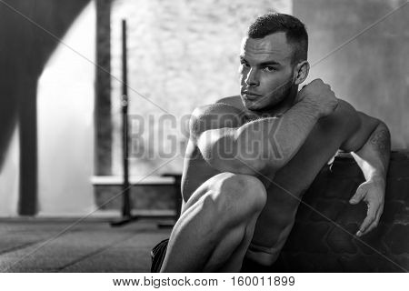 Need some rest. Handsome brutal well built man sitting in front of a huge tire and looking at you while resting after an intensive workout