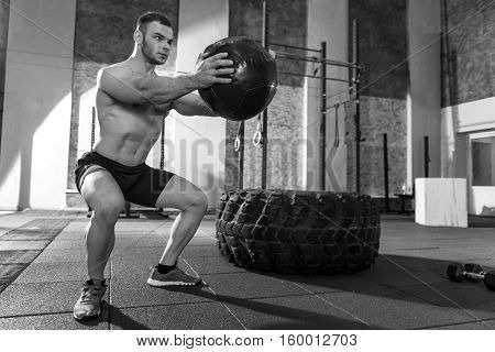 Special sports equipment. Muscular nice serious man holding a med ball in front of him and preparing to throw it while developing his muscular power