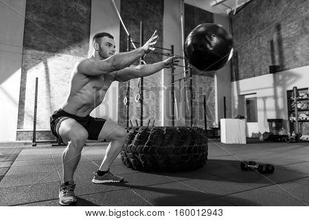 In motion. Handsome nice concentrated man throwing a medicine ball and looking at it while being involved in the gym workout