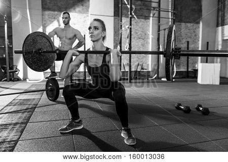 Powerlifting training. Strong well built beautiful woman squatting and holding a barbell while lifting it