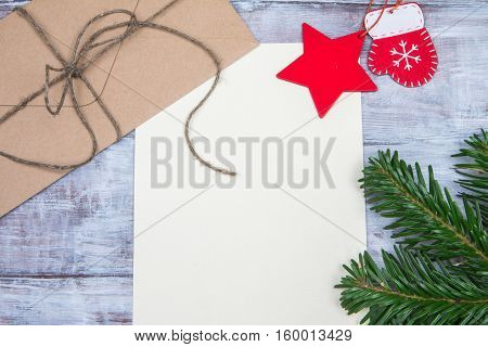 Kraft Envelope, Blank Paper And Christmas Ornaments On Wooden Background