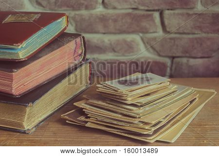 Stack of old family photos and photo albums