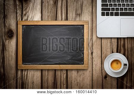 Top view of a laptop empty blackboard and cup of coffee over old wooden desk
