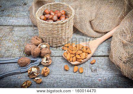 Nuts On A Wooden Table: Hazelnut, Almond, Walnut And Nutcracker