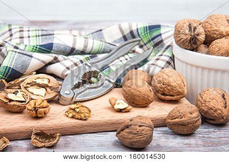 Walnuts, Nutcracker On Cutting Board. Wooden Background