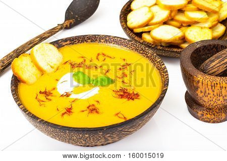 Vegetable cream soup with saffron and croutons on white background. Studio Photo
