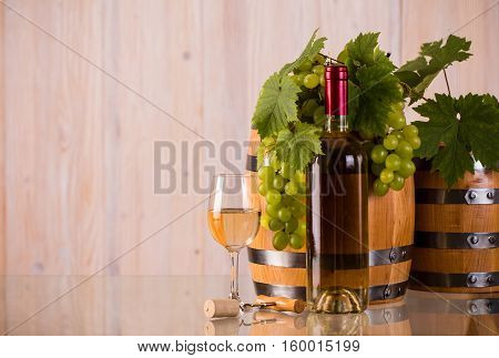 Bottle of white wine with barrels grapes and grapeleaves on glass