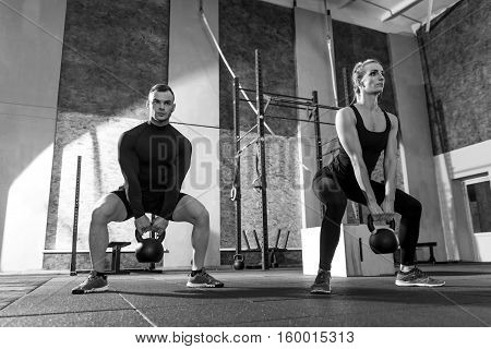 Working out together. Strong good looking well built man and woman holding kettlebells and lifting them while moving synchronically