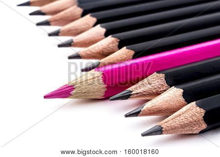 Red colored pencil jutting in row of black pencils, on white background