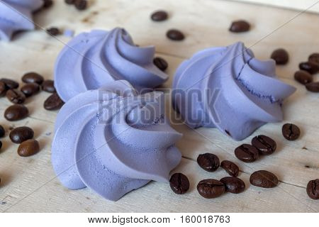 French blue meringue cookies and coffee beans on white wooden background