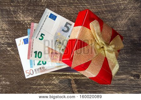 Gift Box with Euro currency on the wooden background