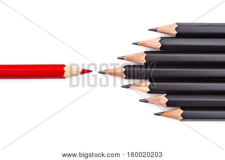 Red and black colored pencils, red pencil trying to break through front of black pencils, on white background