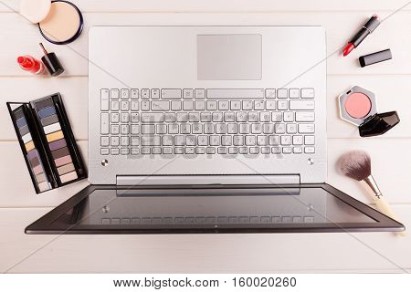 workplace for fashion blogger laptop and cosmetics on the table