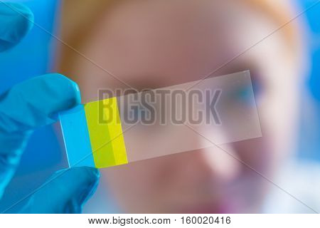 Woman science Assistant in laboratory with microscope slide  of cancer stem cells.