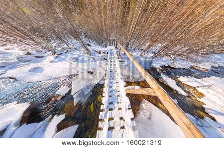 Wide Panorama Of A Wooden Bridge Over The River In The Winter Forest