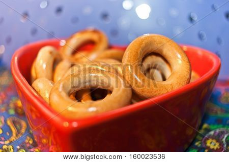 Close-up glazed bagels on red plate in shape of heart on colored background. Selective focus.