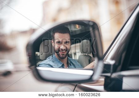 Driver in rear-view mirror. Confident young man smiling and looking at camera while driving a car