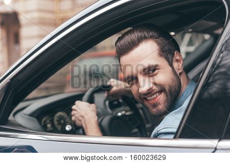 Nice travel. Confident young man smiling and looking at camera while driving a car