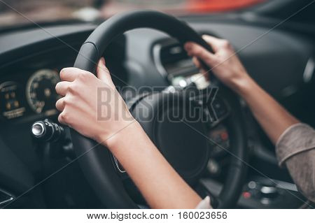 Always on the move. Close-up of female hands on steering wheel while driving a car