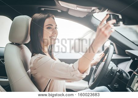One moment for yourself. Young attractive woman smiling and looking at the rear-view mirror while driving a car