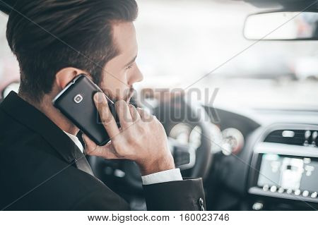 On the phone. Rear view of young handsome man talking on the smart phone while driving a car