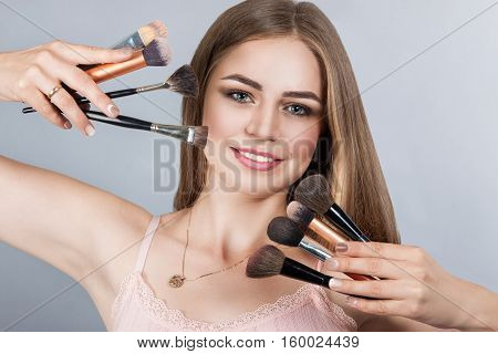 Smiling Woman With Makeup Brushes