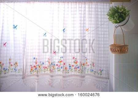 A kitchen windows dressed with lace curtain and flower pot
