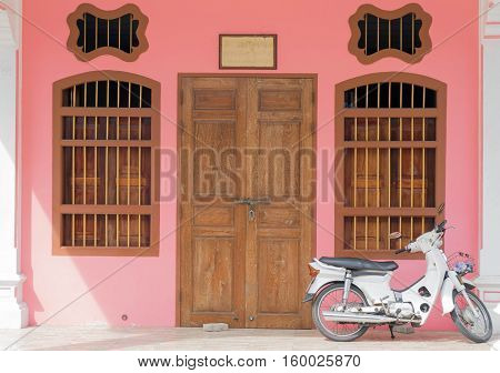 Old pink buildings Sino-Portuguese style with motorcycle in Phuket Thailand. architectural style is European mixed with Chinese modern
