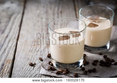 Coffee liqueur in glasses with ice and beans, wood background, copy space