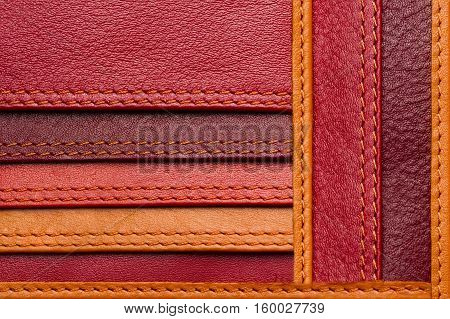 Leather samples with stitches, natural materials with seams of red, maroon, brown, orange colors and other warm shades, woman bag detail, macro shot, selective focus
