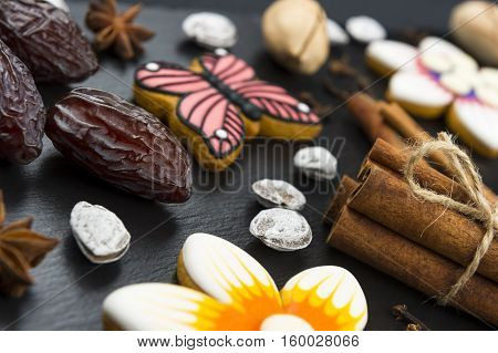 Gingerbread cookies with nuts, dates and spices, colorful homemade cakes in shape of flower and butterfly on black textured background, selective focus