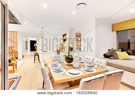 Modern dining set up with wooden table in the living room near to the relaxing area with pillows and cushion mattress beside the kitchen next to wooden stairs and hallway there are lights flashing on the ceiling at night